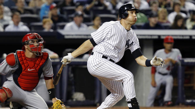 Los Angeles Angels catcher Chris Iannetta watches New York Yankees' Mark Teixeira hit a third-inning RBI double that scored Alex Rodriguez during their baseball game at Yankee Stadium in New York, Sunday, April 15, 2012. (AP Photo/Kathy Willens)