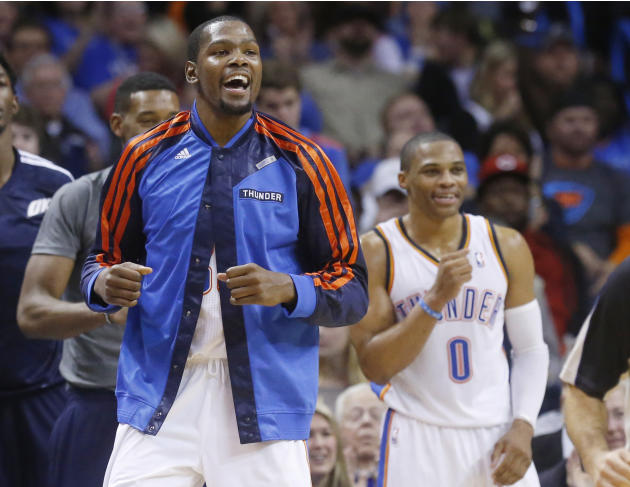 Oklahoma City Thunder forward Kevin Durant, left, and guard Russell Westbrook (0) cheer from the bench in the third quarter of an NBA basketball game against the San Antonio Spurs in Oklahoma City, We