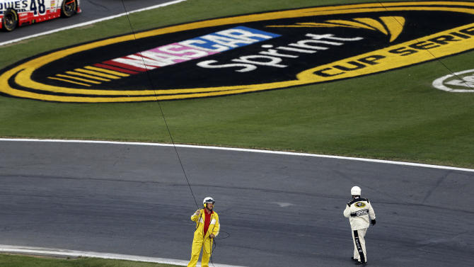 An official and a member of the cleanup crew attend to a broken television cable rig during a red flag in the NASCAR Sprint Cup Series Coca-Cola 600 auto race at the Charlotte Motor Speedway in Concord, N.C., Sunday, May 26, 2013. Several cars were damaged by the broken rig. (AP Photo/Gerry Broome)