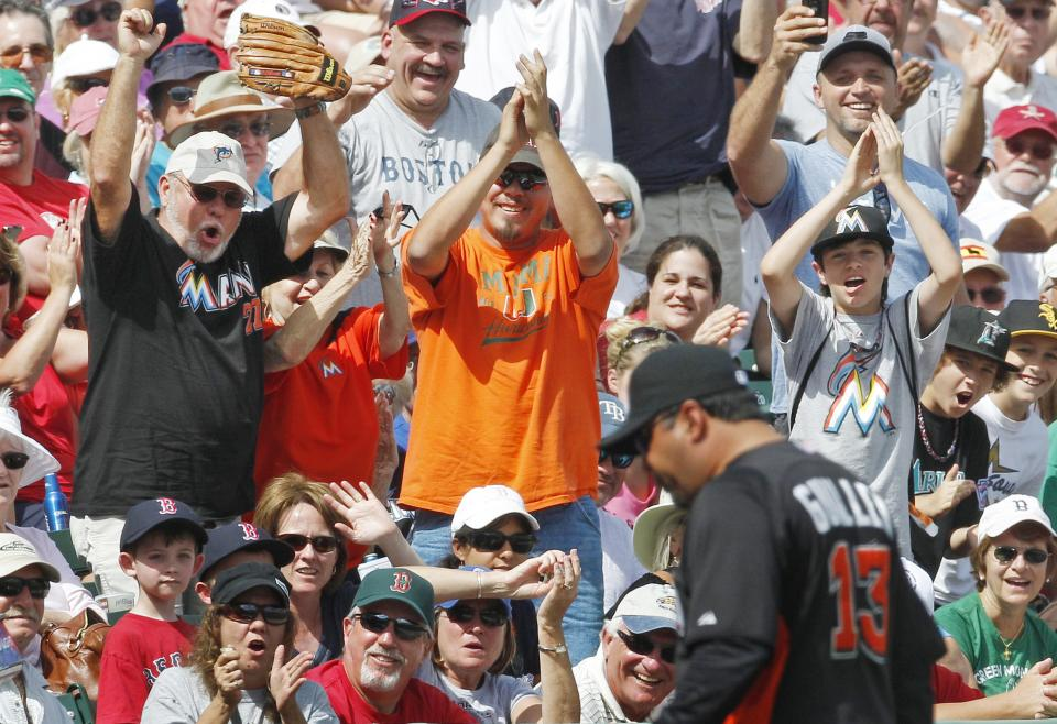 Miami Marlins fans cheer as manager Ozzie Guillen, right, walks off the field after being ejected for arguing a call in the sixth inning of a spring training baseball game against the Boston Red Sox, Monday, March 12, 2012, in Fort Myers, Fla. (AP Photo/Charles Krupa)
