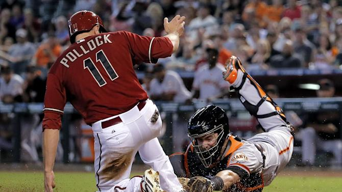 Arizona Diamondbacks' A.J. Pollock (11) scores as San Francisco Giants catcher Andrew Susac dives to make the tag during the fifth inning of a baseball game, Wednesday, Sept. 17, 2014, in Phoenix. Pollock advanced home after catcher Susac dropped the third strike on Mark Trumbo and threw to first for the out. (AP Photo/Matt York)