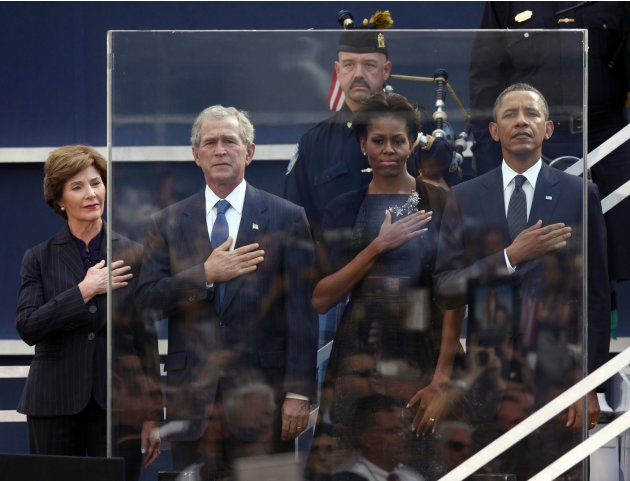 Former first lady Laura Bush, from left, former President George W. Bush, first lady Michelle Obama and President Barack Obama hold hands to their hearts during the national anthem as friends and rela