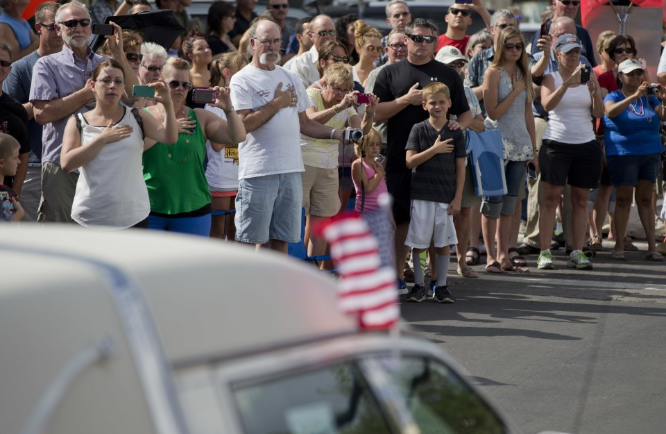 People hold their hands over their hearts to pay their respects as 19 hearses slowly roll by, Sunday, July 7, 2013 in downtown Prescott, Ariz., carrying the 19 Granite Mountain Hotshot firefighters killed a week ago by an out-of-control blaze near Yarnell, Ariz. The nearly five-hour-long procession began near the state Capitol in Phoenix, went through the town where the Granite Mountain Hotshots were killed and ended in the mountain community of Prescott, where they lived and will be laid to rest this week.(AP Photo/Julie Jacobson)