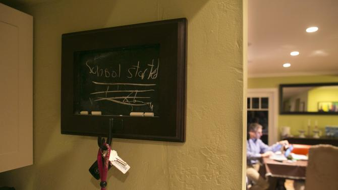 "A chalkboard says ""school started"" in a child's handwriting as Carl Krawitt works on his laptop in his home in Corte Madera, California"