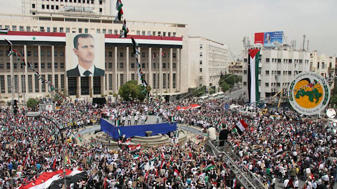 Pro-Syrian government demonstrators hold a rally at Sabe Bahrat Square to commemorate the 65th anniversary of the foundation of the Ruling Baath Arab Socialist Party in Damascus, Syria, Saturday, April 7, 2012. A large picture of President Bashar Assad is seen on the building at left. Syrian President Bashar Assad has accepted a cease-fire deadline brokered by international envoy Kofi Annan, which calls for his forces to pull out of towns and cities by Tuesday and for both government and rebels to lay down their arms by 6 a.m. local time Thursday.(AP Photo Bassem Tellawi)