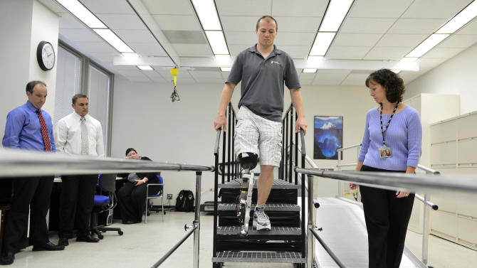 "In this Oct. 25, 2012 photo, physical therapist assistant Suzanne Finucane, right, helps Zac Vawter as he practices walking with an experimental ""bionic"" leg at the Rehabilitation Institute of Chicago. After losing his right leg in a motorcycle accident, the 31-year-old software engineer signed up to become a research subject, helping test a trailblazing prosthetic leg that's controlled by his thoughts. He will put this leg to the ultimate test Sunday, Nov. 4 when he attempts to climb 103 flights of stairs to the top of Chicago's Willis Tower, one of the world's tallest skyscrapers. (AP Photo/Brian Kersey)"