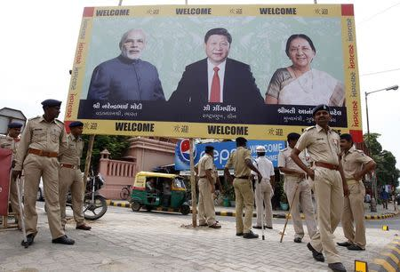 Police personnel stand guard in front of a boarding with images of India's PM Modi, China's President Xi and Patel, Chief Minister of Gujarat, ahead of Xi's arrival in Ahmedabad