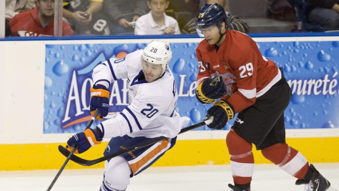 Team Quebec's Eric Belanger, of the Edmonton Oilers, is slowed by Team Montreal's Jason Pominville, of the Buffalo Sabres, during an exhibition hockey game Thursday, Oct. 11, 2012, in Quebec City. Some locked-out NHL players have organized a players' tour to raise funds for local charities. (AP Photo/The Canadian Press, Jacques Boissinot)