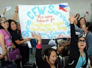 Philippine workers, who had been working in Syria, display a banner as they wait to be processed after disembarking from a plane chartered by the International Organization for Migration at the international airport in Manila