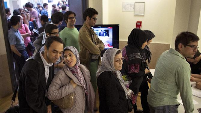 Iranian voters wait on line to cast their ballots at a polling station for Iran's presidential election, Friday, June 14, 2013, in the Queens borough of New York. Iranian-Americans and expatriates will be able to vote Friday, but turnout is expected to be lower than in 2009 in part because there are fewer places to cast ballots. During the previous election, record numbers of Iranians voted in 41 locations throughout the U.S. This year, there are half as many voting locations. (AP Photo/John Minchillo)