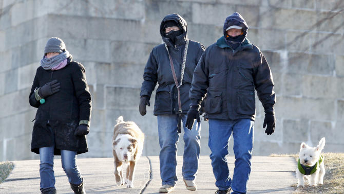 South Boston residents who did not wish to be identified walk their dogs at Castle Island in Boston, Wednesday, Jan. 23, 2013.  The National Weather Service says it's not expected to get above 17 degrees in Boston, with the wind chill making it feel five below. (AP Photo/Michael Dwyer)
