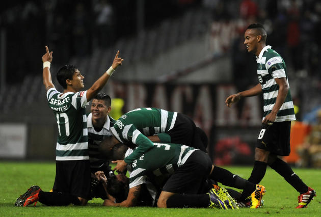 Sporting's Cedric Soares his mobbed by teammates as they celebrate scoring against Sporting Braga during their Portuguese League soccer match at the Municipal Stadium, in Braga, Portugal, Saturday Sep