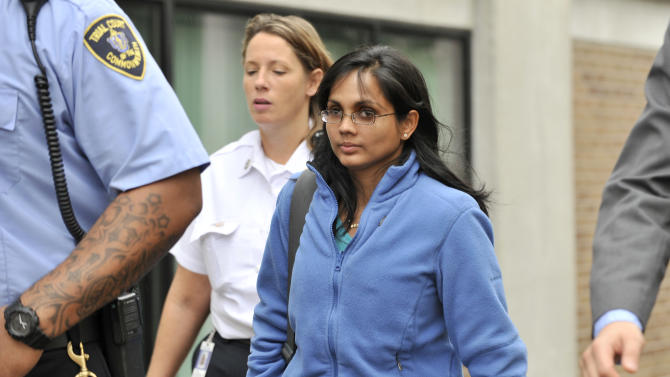 FILE - In a Wednesday, Oct. 10, 2012 file photo, Annie Dookhan, center, is leaves a Boston courthouse escorted by court officers and her lawyer. Dookhan is accused of faking drug results, forging signatures and mixing samples at a state police lab. State police say Dookhan tested more than 60,000 drug samples involving 34,000 defendants during her nine years at Hinton State Laboratory Institute in Boston. (AP Photo/Josh Reynolds, File)