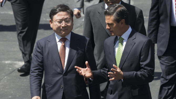 KIA Vice Chairman and CEO Hyoung-Keun Lee, left, and Mexico's President Enrique Pena Nieto talk before an announcement regarding a new KIA Auto assembly plant to be set up in Wednesday, Aug. 27, 2014. KIA announced the construction of a new auto making plant in the northern state of Nuevo Leon which is slated to start operating in 2016. (AP Photo/Eduardo Verdugo)