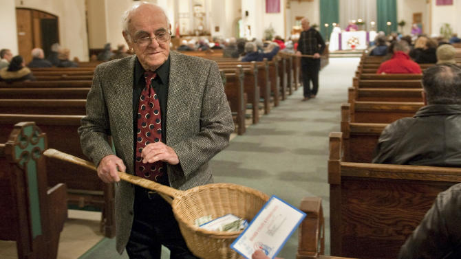 In this Saturday, Dec. 19, 2009 photo, John Alves, of Dartmouth, Mass., uses a basket while taking collection during Mass at St. John the Baptist Roman Catholic Church in New Bedford, Mass. A study on the generosity of Americans, released Monday, Aug. 20, 2012, by the Chronicle of Philanthropy, found that states with populations that are less religious are also the stingiest about giving money to charity. (AP Photo/Gretchen Ertl)