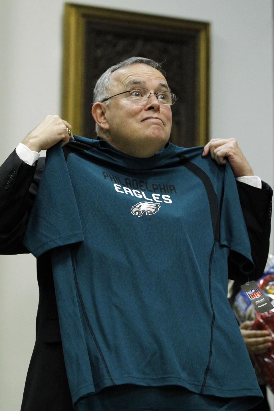 Denver Archbishop Charles Chaput gestures as he displays a Philadelphia Eagles football shirt at a news conference Tuesday, July 19, 2011, in Philadelphia. The Vatican on Tuesday named Chaput Cardinal Justin Rigali's successor as Archbishop of Philadelphia. (AP Photo/Matt Rourke)