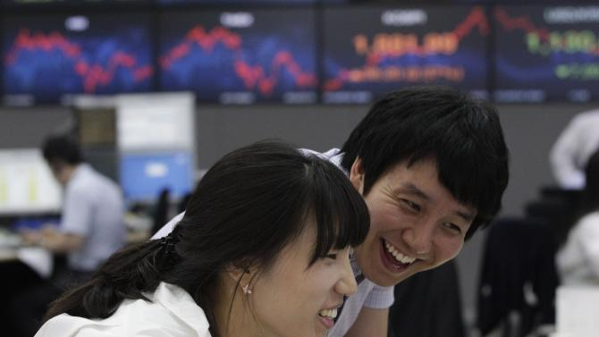 Currency traders smile at the foreign exchange dealing room of the Korea Exchange Bank headquarters in Seoul, South Korea, Tuesday, July 31, 2012. The Korea Composite Stock Price Index rose 2.27 percent, or 38.20, to close at 1,881.99. (AP Photo/Ahn Young-joon)