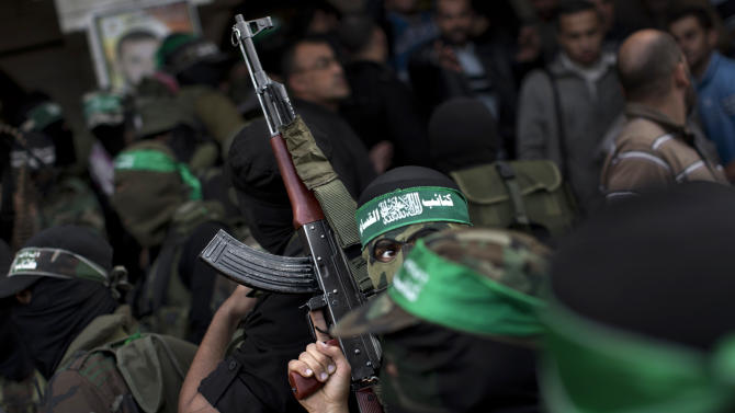 Hamas militants of the Izzedine al-Qassam Brigades attend the funeral of Hamas member Joudeh Shamallah in Gaza City, Saturday, Nov. 24, 2012. According to family members, Shamallah was badly injured during the latest Israeli-Hamas fight and died from wounds Saturday. (AP Photo/Bernat Armangue)
