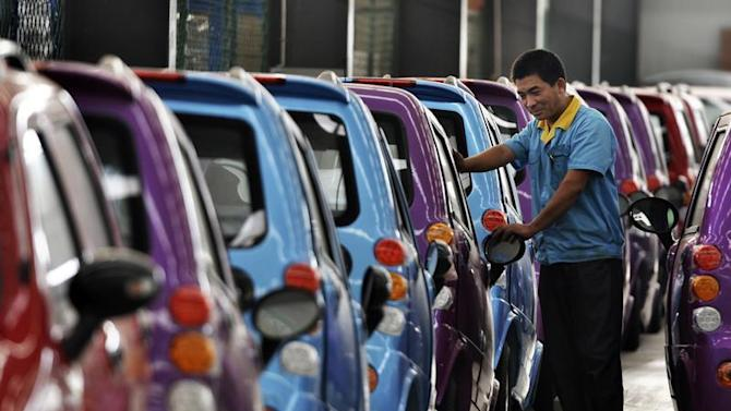 An employee checks newly-assembled electric cars to be exported to South America at an electric vehicle factory in Zouping county