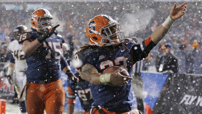 Syracuse running back Prince-Tyson Gulley (23) and guard Zack Chibane (75) celebrate Gulley's third-quarter touchdown against West Virginia in the Pinstripe Bowl NCAA college football game at Yankee Stadium in New York, Saturday, Dec. 29, 2012. Syracuse won 38-14. (AP Photo/Kathy Willens)