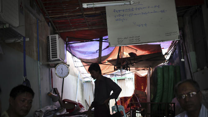 "In this Tuesday, Aug. 13, 2013 photo, actors wait in their dimly lit office in downtown Yangon, Myanmar. Each morning, the bad guys of Yangon and their brethren - all members of Ko Lu Chaw, or ""Handsome Guy Group,"" effectively a trade union for cinematic villains - arrive at dawn. They take up position at outdoor breakfast stalls along 35th and 36th streets, a tightly packed enclave of video production houses, movie-poster design studios and worse-for-wear apartment buildings that serves as the tattered ground zero of the Burmese movie industry. Hoping for day work, they order coffee or tea, and they hope. (AP Photo/Wong Maye-E)"