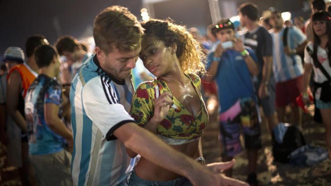 A woman from Brazil and a man from Argentina dance samba at the World Cup Fan Fest 2014, on Copacabana beach, in Rio de Janeiro, Brazil, Wednesday, July 9, 2014. The flood of foreign football fans, the vast majority of them men, has been a boon for the single ladies of Brazil, where a demographic imbalance means women outnumber men by more than 4 million nationally. (AP Photo/Silvia Izquierdo)