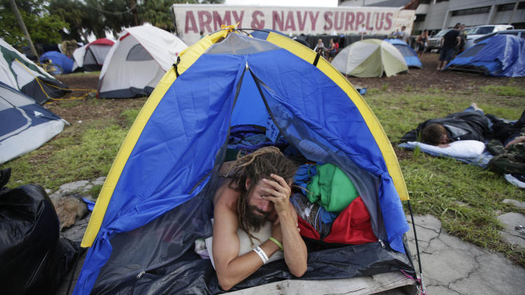 "A demonstrator prepares to leave his tent, Tuesday, Aug. 28, 2012, in Tampa, Fla. Protestors gathered in a camp called ""Romneyville,"" in Tampa to march in demonstration against the Republican National Convention. (AP Photo/Dave Martin)"