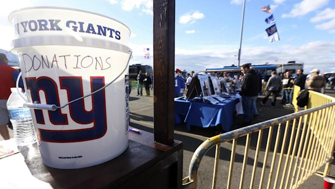 A donation bucket for people suffering from the affects Superstorm Sandy and cystic fibrosis sits on a table near the tailgating area before an NFL football game between the New York Giants and the Pittsburgh Steelers, Sunday, Nov. 4, 2012, in East Rutherford, N.J. (AP Photo/Julio Cortez)