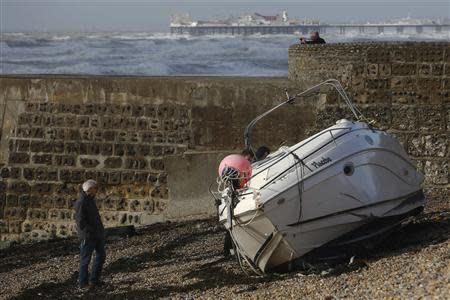 A man walks alongside a yacht washed up on the beach after storms battered Brighton in south east England
