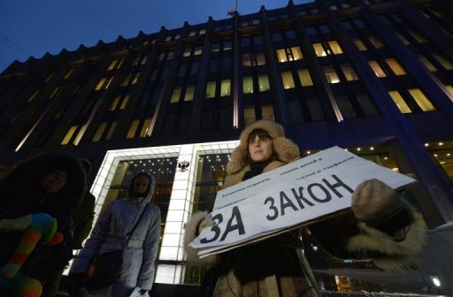 "A woman holds a poster reading ""We support the bill"" outside the upper house of Russia's parliament on December 26, 2012. Russia's upper house of parliament on Wednesday unanimously backed a bill barring Americans from adopting Russian children, leaving the controversial measure in the hands of President Vladimir Putin."