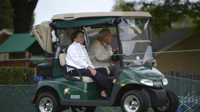 Arnold Palmer, right, and his wife, Kit, ride along the second fairway, while surveying damage to the course, after a severe thunderstorm caused a suspension of play during the final round of the Arnold Palmer Invitational golf tournament in Orlando, Fla., Sunday, March 24, 2013.(AP Photo/Phelan M. Ebenhack)