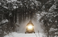 A snowmobile travels a newly-groomed trail on Monday, Dec. 31, 2012 in East Montpelier, Vt. The big snow is giving a big boost to snowmobilers across Vermont, New Hampshire and Maine. Parts of the region have received two feet of snow and more over the last several days, giving a boost to the sport that was hampered last season by a near-snowless winter. (AP Photo/Toby Talbot)