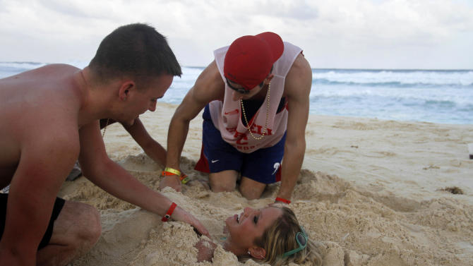 In this March 7, 2012 photo, people bury eachother in the sand on the beach during Spring Break in Cancun, Mexico. While American tourism to Mexico slipped a few percentage points last year, the country remains by far the biggest tourist destination for Americans, according to annual survey of bookings by the largest travel agencies. (AP Photo/Israel Leal)