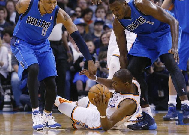 Dallas Mavericks forward Shawn Marion (0) and center Samuel Dalembert (1) reach for the ball held by Oklahoma City Thunder forward Kevin Durant (35) in the first quarter of an NBA basketball game in O