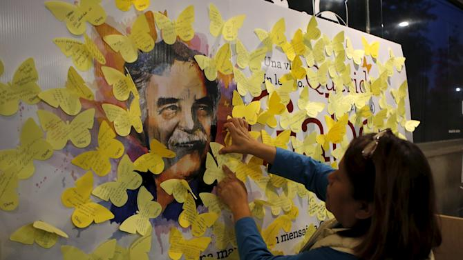 A fan sticks a yellow paper butterfly cutout with messages on a banner with an image of Nobel Prize-winning novelist Gabriel Garcia Marquez, on the first anniversary of his death, at a bookstore in Mexico City