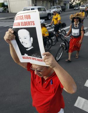 Demonstrators march to the Hawaii Convention Center, site of the APEC Summit in Honolulu, on Tuesday, Nov. 8, 2011, to honor Kollin Elderts, who was allegedly shot and killed by a federal agent. The agent was in Honolulu to help with security at this week's Asia-Pacific Economic Cooperation summit. (AP Photo/Chris Carlson)
