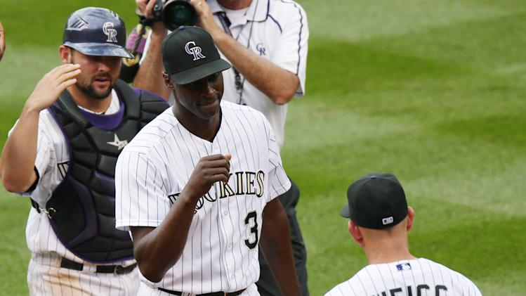 Colorado Rockies relief pitcher LaTroy Hawkins, center, is congratulated by manager Walt Weiss, right, as catcher Michael McKenry looks on after Hawkins retired the Washington Nationals in the ninth inning of the Rockies' 6-4 victory in a baseball game in Denver, Wednesday, July 23, 2014. (AP Photo)