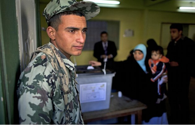 An Egyptian army soldier guards the site of a polling station as a women casts her vote during the second round of a referendum on a disputed constitution drafted by Islamist supporters of president M