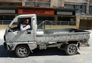 A Syrian civilian drives a bullet-ridden vehicle in the northern city of Aleppo