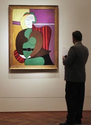 """In this Feb. 14, 2013 photo, an attendee checks out Pablo Picasso's """"The Red Armchair"""" during a media preview for """"Picasso and Chicago,"""" a major exhibition showcasing the works of Picasso at the Art Institute of Chicago. More than 250 works will be on display at the exhibit running Feb. 20-May 12, 2013. The Art Institute was the first museum in the nation to feature Picasso's work a century ago in 1913. Today's exhibit features paintings, drawings, works on paper, ceramics and sculptures. (AP Photo/Caryn Rousseau)"""