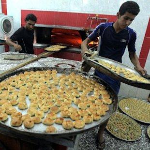 IRAQ, Baghdad : Iraqi men bake cakes and sweets for the occasion of Eid al-Fitr on August 19, 2012 in Baghdad's Sadr City neighborhood. Muslims around the world celebrate Eid al-Fitr, marking the end of Ramadan, the Muslim calendar's ninth and holiest month during which followers are required to abstain from food, drink and sex from dawn to dusk . AFP PHOTO/AHMAD AL-RUBAYE