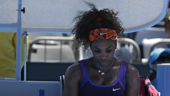Serena Williams of the US is attended to by a trainer after falling during her first round match against Romania's Edina Gallovits-Hall  at the Australian Open tennis championship in Melbourne, Australia, Tuesday, Jan. 15, 2013. (AP Photo/Rob Griffith)