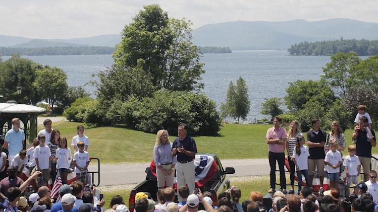 """In this July 4, 2012 photo, Republican presidential candidate Mitt Romney and wife Ann stand with other family members at Brewster Academy during a rally at the end of the Fourth of July Parade in Wolfeboro, N.H. Romney's large family is at the center of his life _ and of his presidential campaign. At a time when nontraditional families have become the norm _ and when even the Romneys are watching """"Modern Family,"""" a popular sitcom that centers on unconventional family arrangements _ the Romney brood stands out. (AP Photo/Charles Dharapak)"""