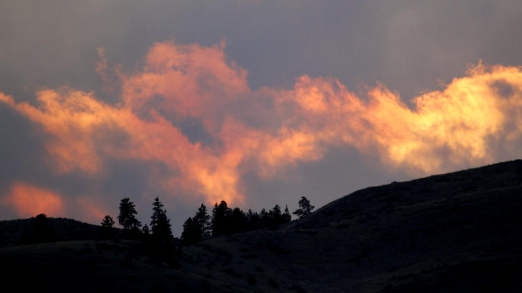 Clouds turn  red from the setting sun where a wildfire burns nearby Monday evening, Sept. 10, 2012, near Wenatchee, Wash. Crews in central Washington and Wyoming worked Monday to protect homes from two of the many wildfires burning throughout the West as a destructive fire season stretches into September with no relief expected from the weather anytime soon. The National Weather service issued red-flag warnings for wide swaths of eastern Washington and Oregon, Idaho, Montana and all of Wyoming, meaning conditions could exacerbate blazes. (AP Photo/Elaine Thompson)