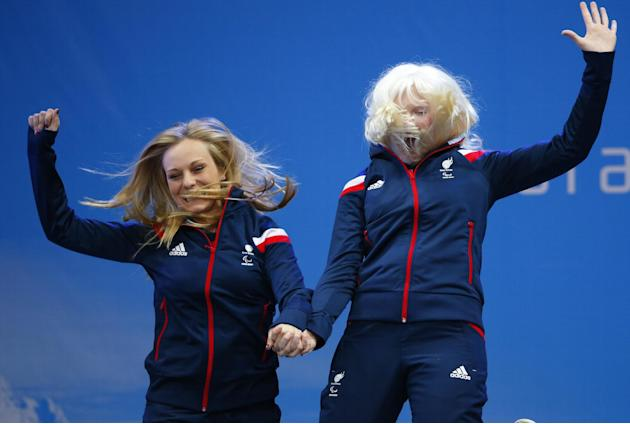 Great Britain's Kelly Gallagher, right, and her guide Charlotte Evans, celebrate their gold medal in the women's alpine skiing, Super-G, visually Impaired event  during a medal ceremony at the