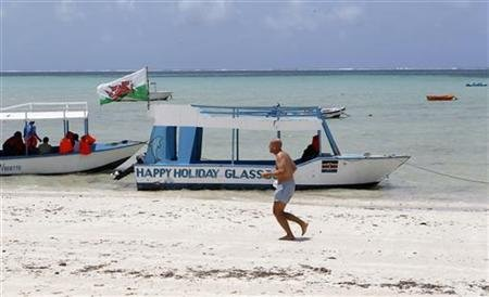 A tourist runs along a deserted beach near the Indian Ocean in the Kenyan coastal city of Mombasa, in this file photo taken August 30, 2012. REUTERS/Thomas Mukoya