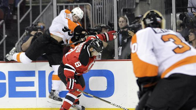 New Jersey Devils' Dainius Zubrus (8), of Lithuania, is checked by Philadelphia Flyers' Brayden Schenn (10) as goalie Ilya Bryzgalov, right, of Russia, watches during the second period of Game 3 of a second-round NHL hockey Stanley Cup playoff series, Thursday, May 3, 2012, in Newark, N.J. (AP Photo/Julio Cortez)