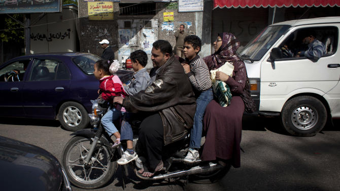 An Egyptian family uses a motorcycle for transportation, during a day of general strikes, in Port Said, Egypt, Friday, Feb. 22, 2013. In the restive city of Port Said, where a general strike entered its sixth day on Friday, factory workers, activists and laborers have held street rallies that brought the coastal city on the northern tip of the Suez Canal to a halt, though shipping in the international waterway has not been affected. (AP Photo/Nasser Nasser)