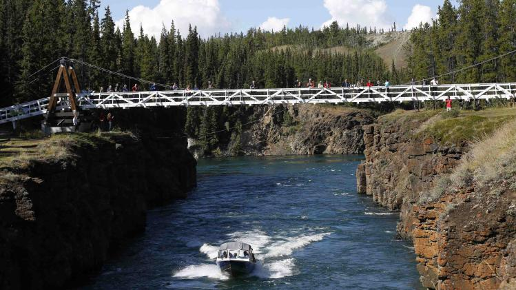 A boat carrying Canada's Prime Minister Harper passes through Miles Canyon on the Yukon River near Whitehorse, Yukon
