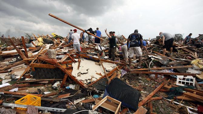 Workers look for victims under debris from a tornado that passed across south Oklahoma City, Monday, May 20, 2013. A monstrous tornado roared through the Oklahoma City suburbs, flattening entire neighborhoods with winds up to 200 mph, setting buildings on fire and landing a direct blow on an elementary school. (AP Photo/The Oklahoman, Paul Hellstern)
